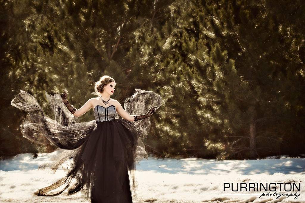 Teen model throwing tulle dress with snow and pine trees